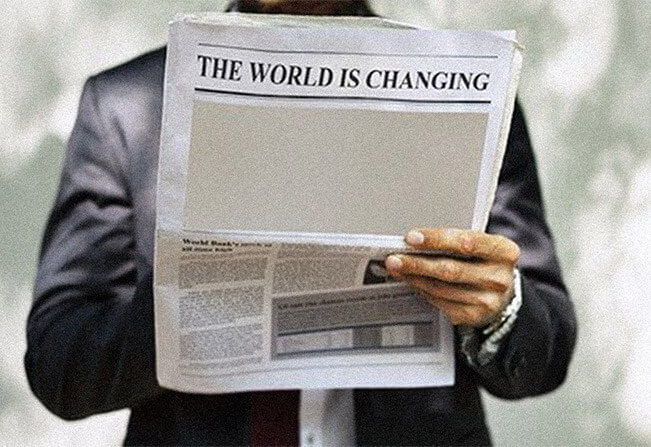 Man reading newspaper that says the world is changing